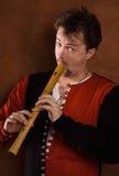 El hombre en un juego medieval toca una flauta Fotografía de archivo libre de regalías