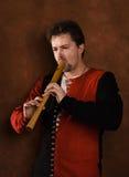 El hombre en un juego medieval toca una flauta Fotos de archivo libres de regalías