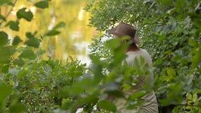 El hombre en un pescador del sombrero, y una muchacha está pescando en el banco del río, lago almacen de metraje de vídeo