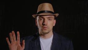 El hombre en un sombrero y una chaqueta toca el vidrio metrajes
