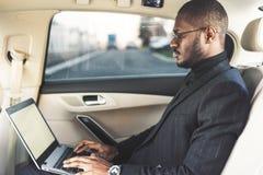 El hombre en un traje de negocios escribe en el ordenador port?til en el sal?n de un coche costoso con el interior de cuero imagen de archivo