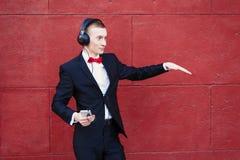 El hombre en un traje está bailando El individuo joven está escuchando la música en auriculares grandes con smartphone Concepto d imágenes de archivo libres de regalías