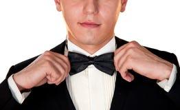 El hombre en un traje negro ajusta su cara del primer de la corbata de lazo Fotografía de archivo libre de regalías