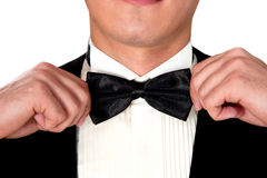 El hombre en un traje negro ajusta su cara del primer de la corbata de lazo Imágenes de archivo libres de regalías