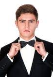 El hombre en un traje negro ajusta su corbata de lazo Imagenes de archivo