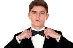 El hombre en un traje negro ajusta su primer de la corbata de lazo Fotografía de archivo libre de regalías