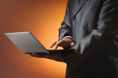 El hombre en un traje trabaja en un ordenador portátil Fotos de archivo libres de regalías