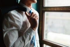 El hombre en una camisa blanca con un lazo azul sostiene una chaqueta en su hombro, colocándose delante de la ventana El hombre d imagen de archivo libre de regalías