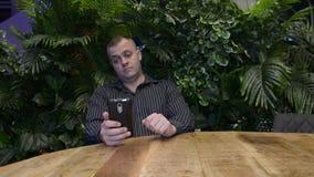 el hombre en una camisa larga del negro de la manga que se sienta en un café del verano y comunica emocionalmente por el teléfono metrajes
