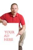 El hombre en una camisa roja lleva a cabo una muestra blanca del anuncio de la tarjeta Fotografía de archivo libre de regalías