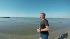 El hombre en una camiseta negra corre a lo largo de la orilla almacen de video
