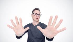 El hombre en una camiseta negra y vidrios tiene miedo, haciendo la parada con sus manos Emoci?n profunda del concepto del miedo foto de archivo