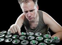 El hombre en una camiseta verde y varias latas de cerveza vacías en un fondo negro Imágenes de archivo libres de regalías