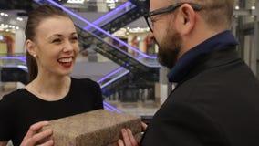 El hombre en una chaqueta está dando el regalo a la mujer joven y ella lo abraza en la tienda interior Ella está sonriendo metrajes