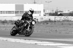 El hombre en una chaqueta negra y los pantalones grises compiten con en una motocicleta imagen de archivo