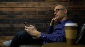 El hombre en una silla suave usando el teléfono bebe el café almacen de metraje de vídeo