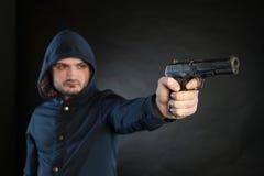 El hombre en una sudadera con capucha está señalando una arma de mano en la blanco Imagen de archivo libre de regalías
