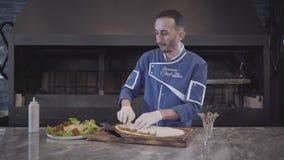 El hombre en el uniforme del cocinero que preparaba el plato envolvió en lavash La mano del cocinero que se separa cuidadosamente metrajes