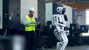 El hombre en workwear está actuando un robot con una tableta almacen de video