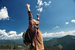 El hombre encantado está disfrutando entre altos paisajes imagenes de archivo