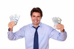 El hombre encantador que sonríe y que le muestra cobra el dinero Foto de archivo libre de regalías