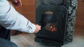 El hombre enciende la estufa en sauna, estufa de madera en sauna almacen de video