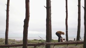 El hombre enciende los carbones en el bosque del brasero y la mujer del hd del mar sale almacen de metraje de vídeo