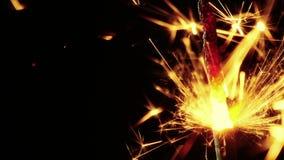 El hombre enciende para arriba los fuegos artificiales que queman en un fondo negro, enhorabuena, saludos, partido, Feliz Año Nue almacen de metraje de vídeo