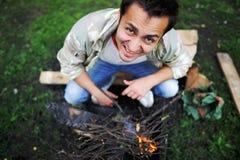 El hombre enciende un fuego en madera del verano foto de archivo libre de regalías