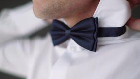 El hombre endereza el cuello de su primer de la camisa Un hombre en una camisa blanca metrajes