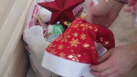 El hombre endereza su pequeño árbol de navidad que brilla intensamente hermoso almacen de metraje de vídeo