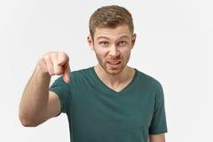 El hombre enfadado le acusa, puntos derecho en la cámara, estando enojado, culpa sus fracasos, gritos en alta voz de cólera fotos de archivo