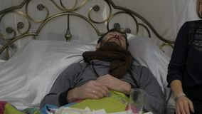 El hombre enfermo triste con una bufanda caliente alrededor de su cuello, mujer trae píldoras y un termómetro Cámara lenta almacen de video