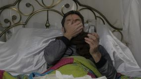 El hombre enfermo triste con una bufanda caliente alrededor de su cuello, mujer trae píldoras y un termómetro Cámara lenta metrajes