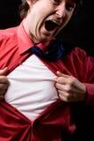 El hombre enfurecido rasga apagado una camisa roja Foto de archivo libre de regalías