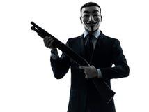 El hombre enmascaró al miembro anónimo del grupo que sostenía la silueta po de la escopeta imágenes de archivo libres de regalías