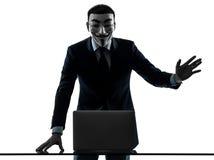 El hombre enmascaró el ordenador computacional del miembro anónimo del grupo que saludaba el si imagen de archivo libre de regalías