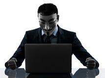 El hombre enmascaró la silueta computacional del ordenador del miembro anónimo del grupo foto de archivo