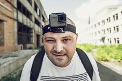 El hombre enojado con la cámara de la acción en la cabeza que mira la cámara y va Retrato del blogger del viaje en fondo urbano fotografía de archivo