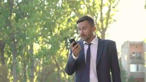 El hombre enojado en el discurso negro en el teléfono, desnudando las gafas de sol y está nervioso almacen de video