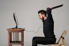 El hombre enojado está destruyendo un teclado fotos de archivo libres de regalías