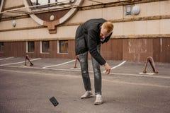 El hombre enojado está lanzando lejos su teléfono móvil Fotos de archivo