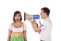 El hombre enojado grita en el oído de la mujer con el megáfono Foto de archivo