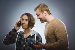 El hombre enojado grita en un adolescente con un teléfono móvil Fotografía de archivo libre de regalías