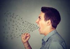 El hombre enojado que grita con alfabeto pone letras al vuelo fuera de boca abierta de par en par fotos de archivo