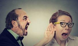 El hombre enojado que grita a la mujer curiosa con la mano al gesto del oído escucha Imagen de archivo