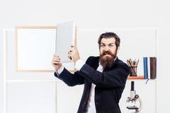 El hombre enojado rompe el ordenador portátil fotos de archivo
