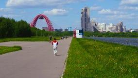 El hombre entra la distancia en el parque que pasa por alto el río almacen de video