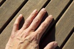 El hombre entrega líneas asoleadas de madera de la teca Imagenes de archivo