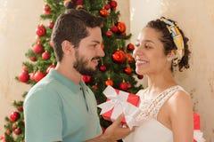 El hombre entrega el regalo de la Navidad a la novia Ella lleva pañuelo i Foto de archivo